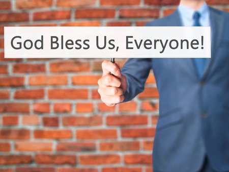 everyone: God Bless Us, Everyone - Businessman hand holding sign. Business, technology, internet concept. Stock Photo Stock Photo