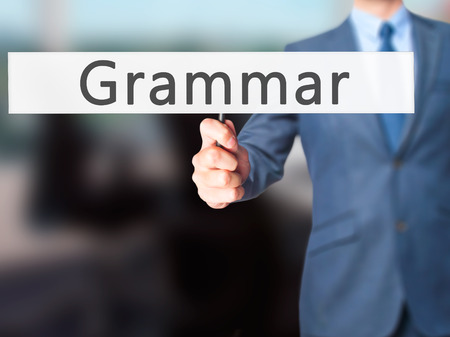 adjective: Grammar - Businessman hand holding sign. Business, technology, internet concept. Stock Photo