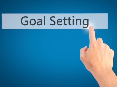 achievable: Goal Setting - Hand pressing a button on blurred background concept . Business, technology, internet concept. Stock Photo Stock Photo