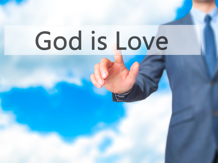 god button: God is Love - Businessman hand pressing button on touch screen interface. Business, technology, internet concept. Stock Photo