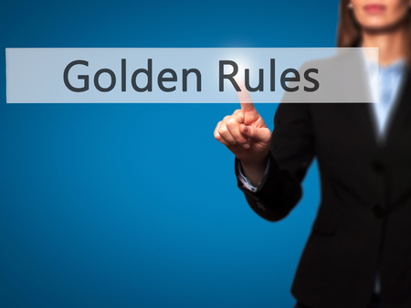 credible: Golden Rules - Businesswoman hand pressing button on touch screen interface. Business, technology, internet concept. Stock Photo