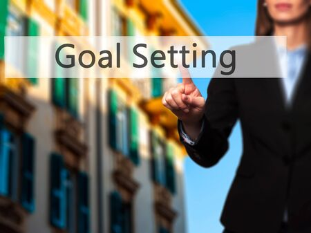 achievable: Goal Setting - Businesswoman hand pressing button on touch screen interface. Business, technology, internet concept. Stock Photo