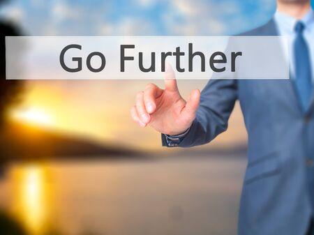 further: Go Further - Businessman hand pressing button on touch screen interface. Business, technology, internet concept. Stock Photo