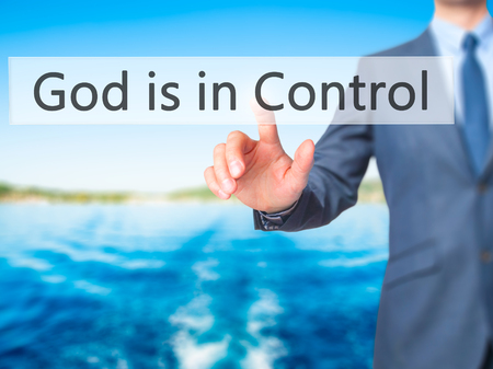 god button: God is in Control - Businessman hand pressing button on touch screen interface. Business, technology, internet concept. Stock Photo