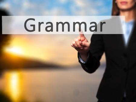 adjective: Grammar - Businesswoman hand pressing button on touch screen interface. Business, technology, internet concept. Stock Photo
