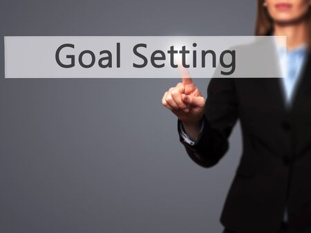 specific: Goal Setting - Businesswoman hand pressing button on touch screen interface. Business, technology, internet concept. Stock Photo