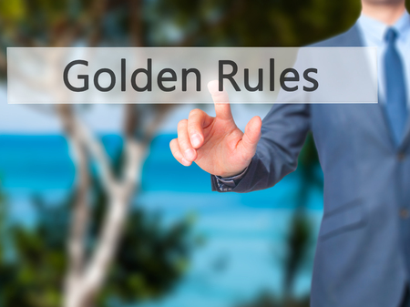 golden rule: Golden Rules - Businessman hand pressing button on touch screen interface. Business, technology, internet concept. Stock Photo
