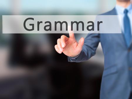 adjective: Grammar - Businessman hand pressing button on touch screen interface. Business, technology, internet concept. Stock Photo