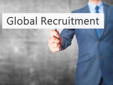 hand holding world: Global Recruitment - Businessman hand holding sign. Business, technology, internet concept. Stock Photo