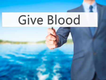 transfused: Give Blood - Businessman hand holding sign. Business, technology, internet concept. Stock Photo