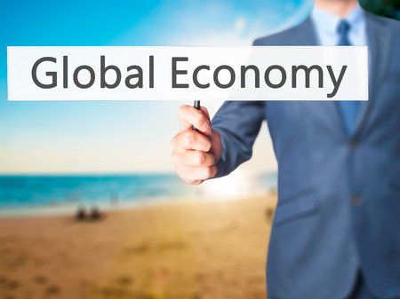 world market: Global Economy - Businessman hand holding sign. Business, technology, internet concept. Stock Photo Stock Photo