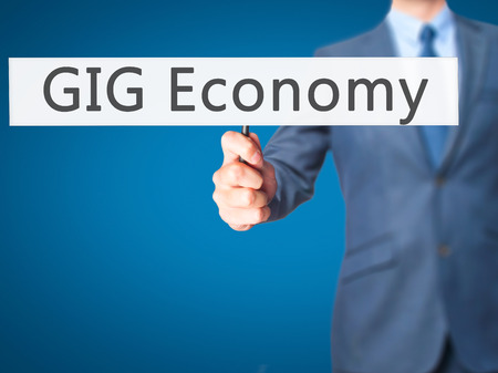 temporary employees: GIG Economy - Businessman hand holding sign. Business, technology, internet concept. Stock Photo Stock Photo
