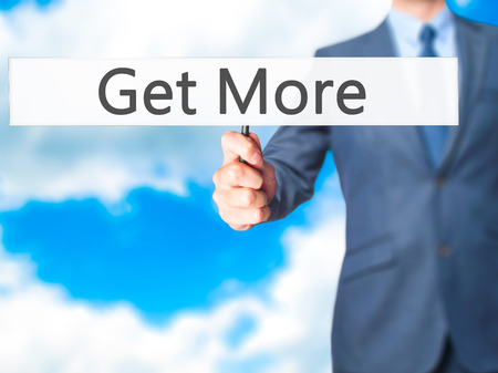 likes: Get More - Businessman hand holding sign. Business, technology, internet concept. Stock Photo