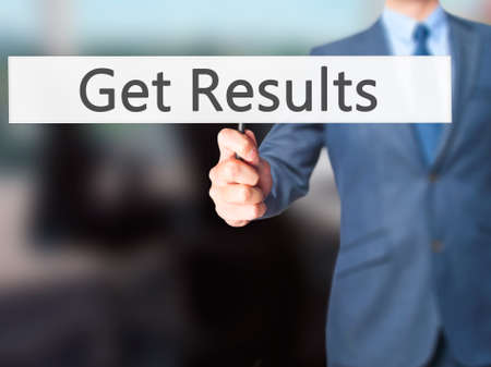 business performance: Get Results - Businessman hand holding sign. Business, technology, internet concept. Stock Photo
