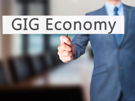 gig: GIG Economy - Businessman hand holding sign. Business, technology, internet concept. Stock Photo Stock Photo