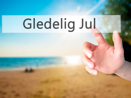december 25th: Gledelig Jul (Happy Christmas in Norwegian) - Hand pressing a button on blurred background concept . Business, technology, internet concept. Stock Photo Stock Photo