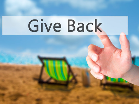 benevolent: Give Back - Hand pressing a button on blurred background concept . Business, technology, internet concept. Stock Photo