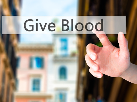 transfused: Give Blood - Hand pressing a button on blurred background concept . Business, technology, internet concept. Stock Photo