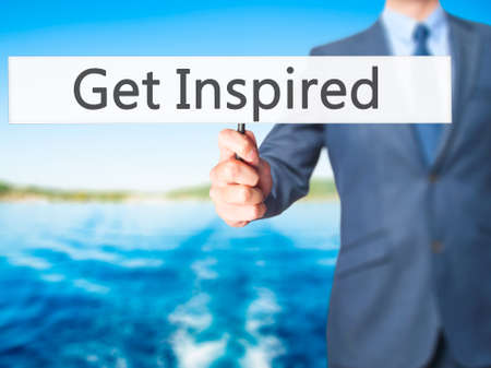 inspired: Get Inspired  - Businessman hand holding sign. Business, technology, internet concept. Stock Photo Stock Photo