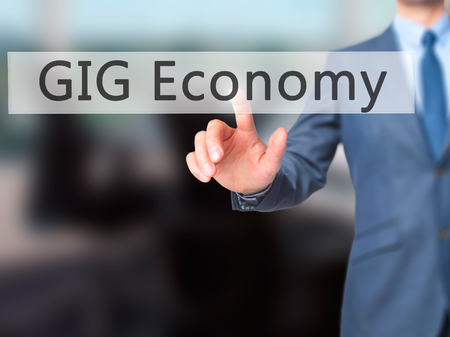 GIG Economy - Businesswoman hand pressing button on touch screen interface. Business, technology, internet concept. Stock Photo Stock Photo