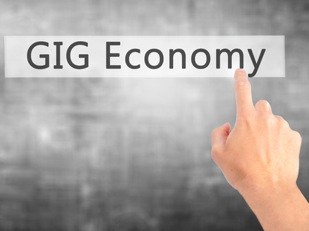 temporary employees: GIG Economy - Hand pressing a button on blurred background concept . Business, technology, internet concept. Stock Photo
