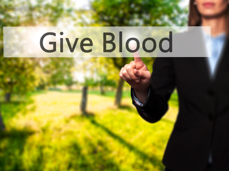 transfused: Give Blood - Businesswoman hand pressing button on touch screen interface. Business, technology, internet concept. Stock Photo