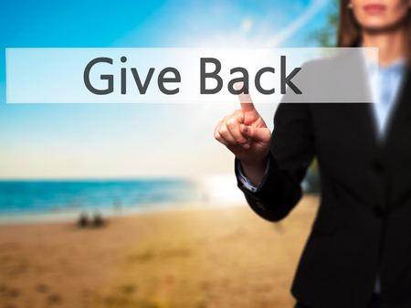 benevolent: Give Back - Businesswoman hand pressing button on touch screen interface. Business, technology, internet concept. Stock Photo Stock Photo