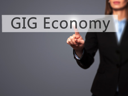 gig: GIG Economy - Businesswoman hand pressing button on touch screen interface. Business, technology, internet concept. Stock Photo Stock Photo