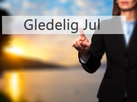 december 25th: Gledelig Jul (Happy Christmas in Norwegian) - Businesswoman hand pressing button on touch screen interface. Business, technology, internet concept. Stock Photo