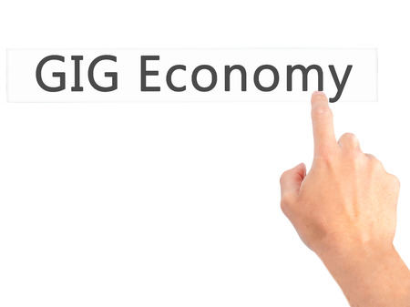 gig: GIG Economy - Hand pressing a button on blurred background concept . Business, technology, internet concept. Stock Photo