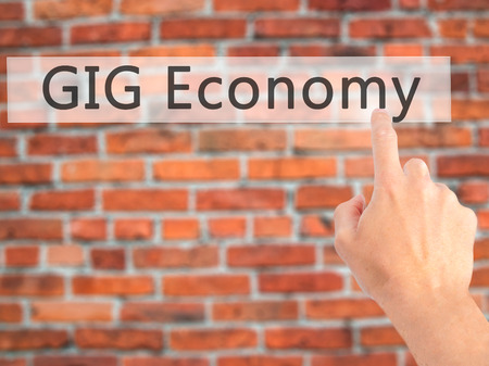 GIG Economy - Hand pressing a button on blurred background concept . Business, technology, internet concept. Stock Photo