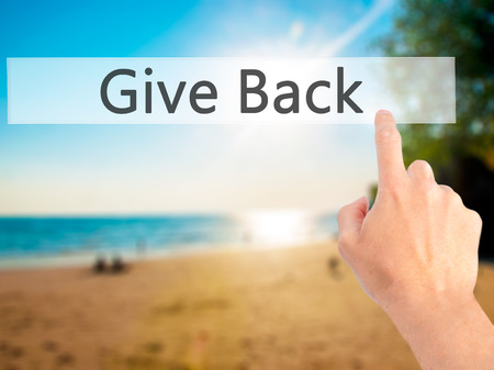 bestowing: Give Back - Hand pressing a button on blurred background concept . Business, technology, internet concept. Stock Photo