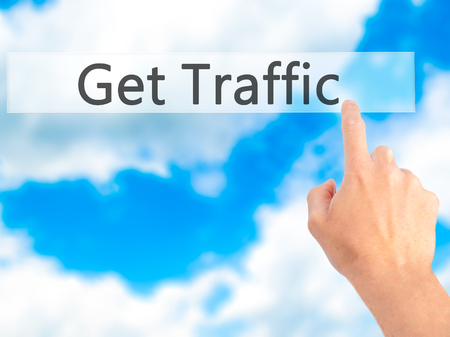 pageviews: Get Traffic - Hand pressing a button on blurred background concept . Business, technology, internet concept. Stock Photo