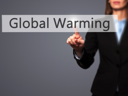 ecological problem: Global Warming - Businesswoman hand pressing button on touch screen interface. Business, technology, internet concept. Stock Photo