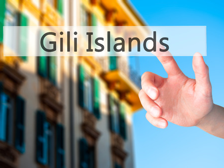 ferien: Gili Islands - Hand pressing a button on blurred background concept . Business, technology, internet concept. Stock Photo