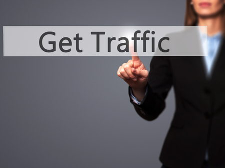 pageviews: Get Traffic - Businesswoman hand pressing button on touch screen interface. Business, technology, internet concept. Stock Photo