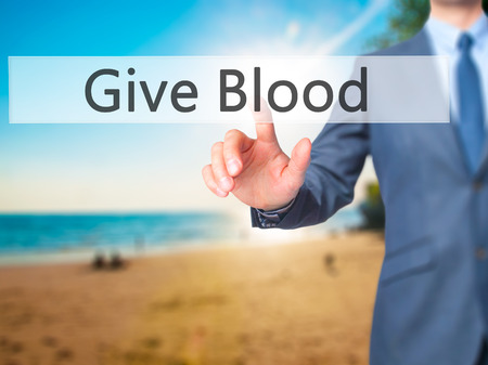 transfused: Give Blood - Businessman hand pressing button on touch screen interface. Business, technology, internet concept. Stock Photo