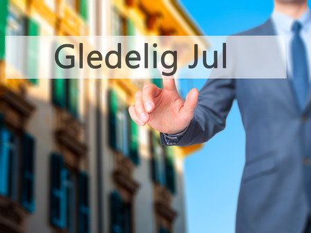 december 25th: Gledelig Jul (Happy Christmas in Norwegian) - Businessman hand pressing button on touch screen interface. Business, technology, internet concept. Stock Photo