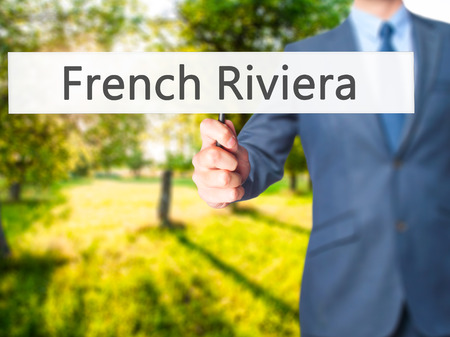 naturist: French Riviera - Businessman hand holding sign. Business, technology, internet concept. Stock Photo