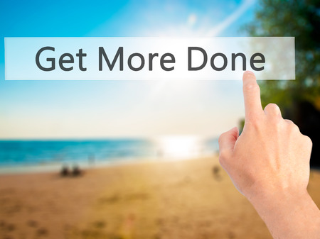 working ethic: Get More Done - Hand pressing a button on blurred background concept . Business, technology, internet concept. Stock Photo
