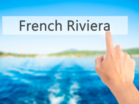 French Riviera - Hand pressing a button on blurred background concept . Business, technology, internet concept. Stock Photo