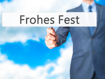 december 25th: frohes fest (Happy Christmas in German) - Businessman hand holding sign. Business, technology, internet concept. Stock Photo