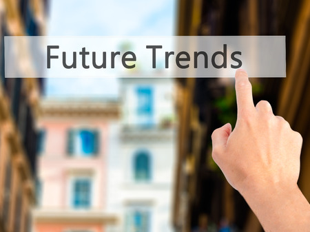 tendency: Future Trends - Hand pressing a button on blurred background concept . Business, technology, internet concept. Stock Photo