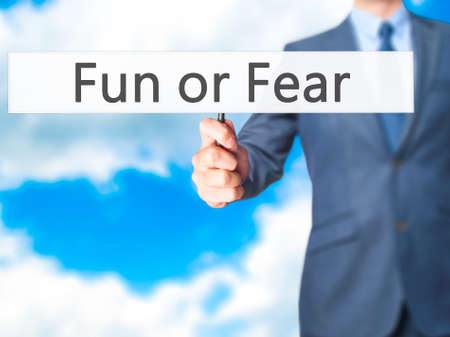 hand holding sign: Fun or Fear - Businessman hand holding sign. Business, technology, internet concept. Stock Photo