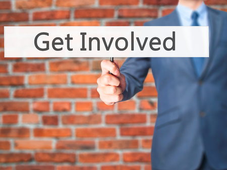 common goals: Get Involved - Businessman hand holding sign. Business, technology, internet concept. Stock Photo