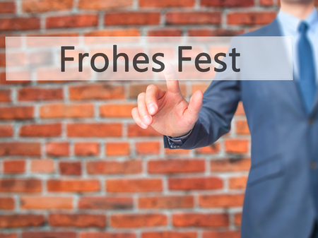 fest: frohes fest (Happy Christmas in German)  - Businessman hand pressing button on touch screen interface. Business, technology, internet concept. Stock Photo Stock Photo