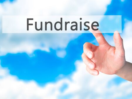 Fundraise - Hand pressing a button on blurred background concept . Business, technology, internet concept. Stock Photo