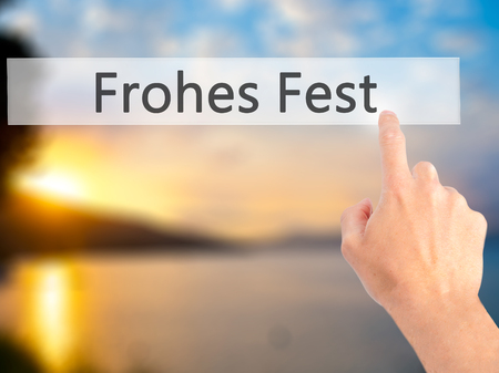 fest: frohes fest (Happy Christmas in German) - Hand pressing a button on blurred background concept . Business, technology, internet concept. Stock Photo Stock Photo