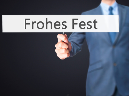 fest: frohes fest (Happy Christmas in German) - Businessman hand holding sign. Business, technology, internet concept. Stock Photo