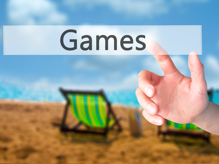 games hand: Games - Hand pressing a button on blurred background concept . Business, technology, internet concept. Stock Photo